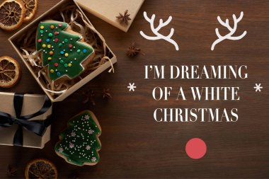 top view of Christmas tree cookie in gift box on wooden table with i am dreaming of a white christmas lettering