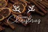 zblízka pohled na sušené pomerančové plátky a skořice na dřevěném pozadí s veselou vánoční ilustrací