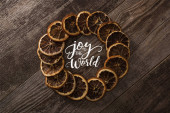 round frame of dried orange slices on wooden background with joy to the world illustration