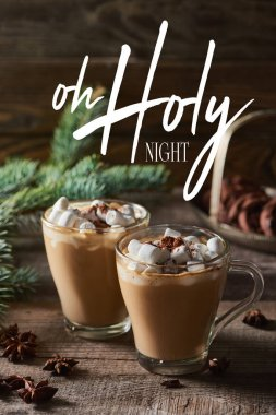 selective focus of cacao with marshmallow and cacao powder in mugs near pine branches, cinnamon and anise on wooden table with oh holy night illustration