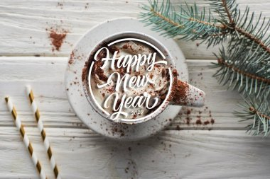 Top view of Christmas cacao with cacao powder and whipped cream in mug on white wooden table near fir branch with happy new year lettering stock vector