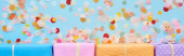 panoramic shot of colorful and wrapped gift boxes near confetti on blue