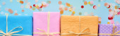 panoramic shot of colorful gift boxes near confetti on blue