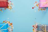 vrchní pohled na zabalené dárky v blízkosti barevné konfety na modré