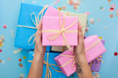 cropped view of woman holding pink gift box near colorful presents near confetti on blue