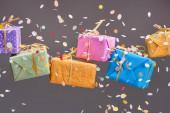 padající konfety v blízkosti barevné dárky na šedé