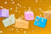 padající konfety v blízkosti barevné dárky na oranžové