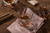 Brandy glasses with map, cigars and matches on wooden table