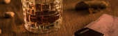 Egy pohár brandy öngyújtóval a térképen, pisztácia és szivar a fa asztalon, panoráma lövés