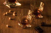 Photo Glasses of brandy with pistachios, cigar and lighter on wooden table
