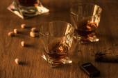 Sklenice brandy s pistáciemi, doutníkem a zapalovačem na dřevěném stole