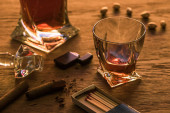 Glass of brandy with cigars, lighter and matches on wooden table