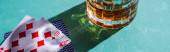 Kijev, Ukrajna - 2019. november 7.: Egy pohár brandy játékkártyával zöld alapon, panoráma felvétel