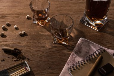 Glasses of brandy, cigars with map and pistachios on wooden table