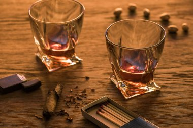 Glasses of brandy with cigar, lighter and pistachios on wooden table