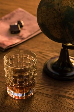 Glass of brandy with globe and lighter on map on wooden table