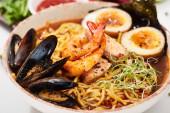 Nahaufnahme von würzigen Meeresfrüchten Ramen mit Muscheln und Garnelen in Schüssel