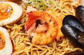 close up view of spicy seafood ramen with shrimps, eggs and mussels