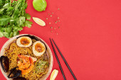 top view of spicy seafood ramen near chopsticks, parsley and lime isolated on red