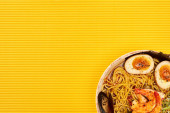 Fotografie top view of seafood ramen on yellow surface