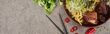 Top view of spicy meat ramen near chili pepper, parsley and chopsticks on grey concrete surface, panoramic shot stock vector