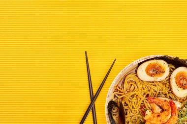 Top view of seafood ramen near chopsticks on yellow surface stock vector