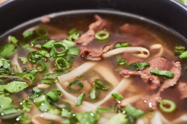 close up view of pho with noodles, meat, cilantro and green onion in bowl