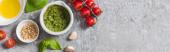 Fotografia top view of raw tomatoes, garlic, basil, pine nuts, olive oil, pesto sauce on grey surface, panoramic shot