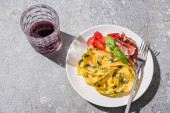 Fotografie vrchní pohled na chutné Pappardelle s rajčaty, pestem a prosciutto s vidličkou v blízkosti červeného vína na šedém povrchu