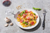 Fotografie Pappardelle s rajčaty, pestem a prosciuttem v blízkosti červeného vína a ingrediencí na šedém povrchu