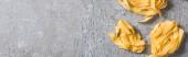 pohled shora na surový Pappardelle na šedém povrchu, panoramatický záběr