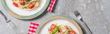 Top view of Pappardelle with tomatoes, basil and prosciutto on plates on plaid napkins with forks on grey surface, panoramic shot stock vector
