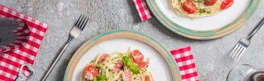 Top view of Pappardelle with tomatoes, basil and prosciutto on plates on plaid napkins with forks near red wine on grey surface, panoramic shot stock vector