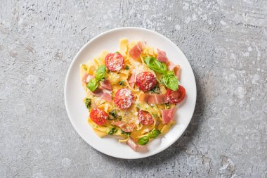 Top view of cooked Pappardelle with tomatoes, pesto sauce and prosciutto on grey surface stock vector