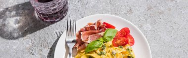 Top view of tasty Pappardelle with tomatoes, pesto and prosciutto with fork near red wine on grey surface, panoramic shot stock vector