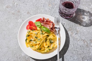 Top view of tasty Pappardelle with tomatoes, pesto and prosciutto with fork near red wine on grey surface stock vector