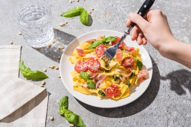 Partial view of woman eating tasty Pappardelle with tomatoes, pesto and prosciutto near water on grey surface stock vector
