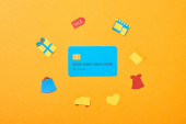 top view of blue credit card template near shopping icons isolated on orange