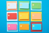 horní pohled na vícebarevné prázdné kreditní karty na modrém pozadí