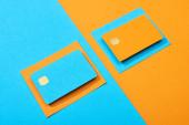 barevné prázdné kreditní karty na modrém a oranžovém pozadí