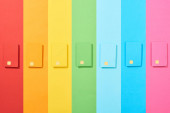 top view of multicolored empty credit cards on rainbow background