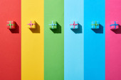 top view of multicolored gift boxes on rainbow background