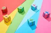 multicolored gift boxes scattered on rainbow background