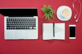 lapos feküdt okostelefon, laptop, fülhallgató, kávé, notebook toll és növény piros háttér