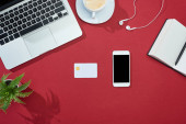 top view of credit card, smartphone, laptop, earphones, coffee, notebook and plant on red background