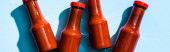 Horní pohled na láhve s chutnou rajčatovou omáčkou na modrém pozadí, panoramatický záběr