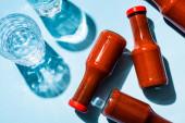 Draufsicht auf zwei Gläser Wasser mit Tomatensauce in Flaschen auf blauem Hintergrund
