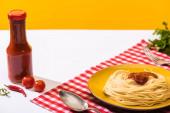 Fotografie Rajčatová omáčka vedle chutných špaget na bílém povrchu na žlutém pozadí
