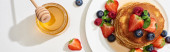 pohled na vynikající palačinky s medem, borůvky a jahodami na talíři na mramorovém bílém povrchu, panoramatický záběr