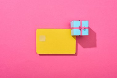 Top view of yellow empty credit card with gift box on pink background stock vector